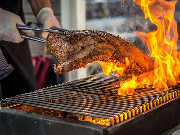Beispielbild Grill, Flammen schlagen hoch, Steak wird gewendet - Handwerk